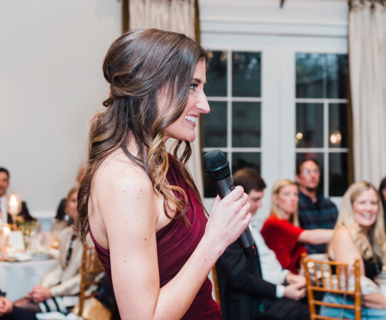 A side view of a woman wearing a burgundy dress reading a speech to guests at a wedding