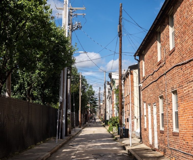 An alleyway with a brick wall with trees peering over it on the left and the backs of brick houses on the right with a few puffed clouds scattered across a blue sky