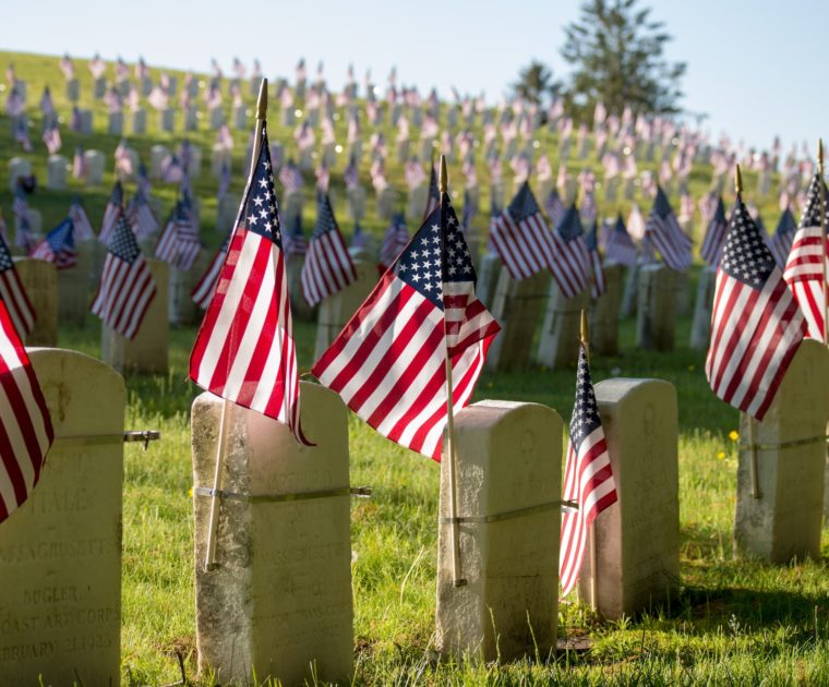 A cemetery filled with small, blurred tombstones and small American flags on sticks attached to each tombstone
