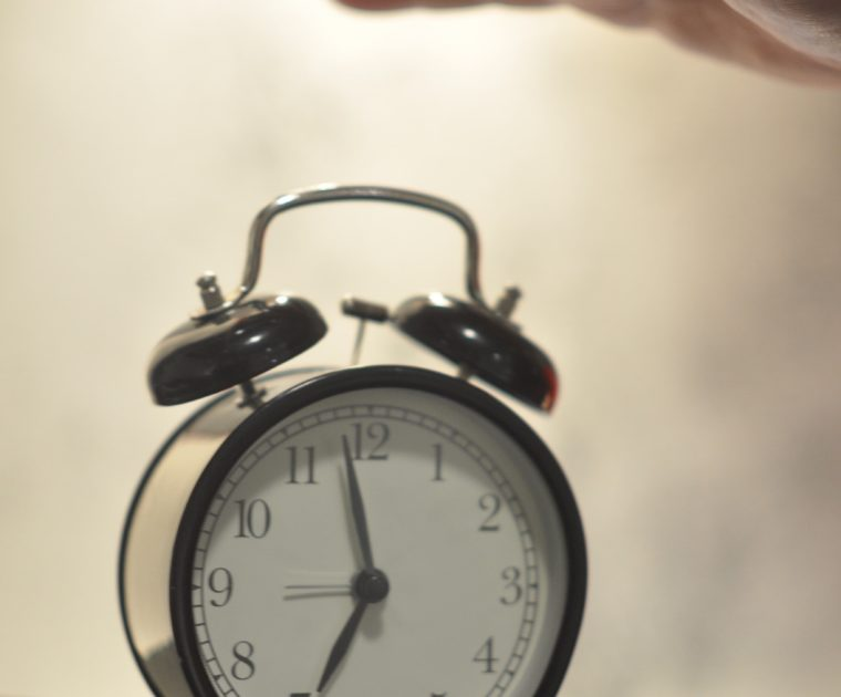 A hand is extended above an alarm clock