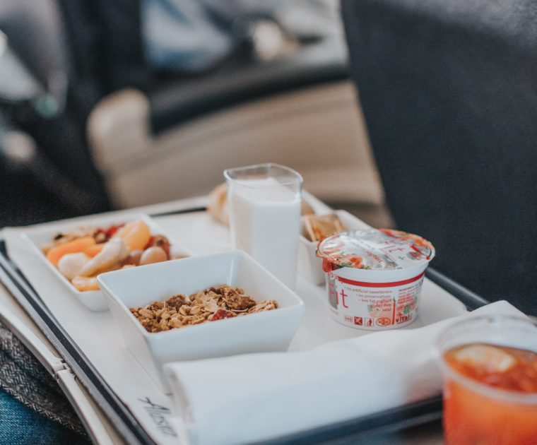 A first class flight breakfast meal tray that includes granola, fruit, bread, butter and a glass of milk
