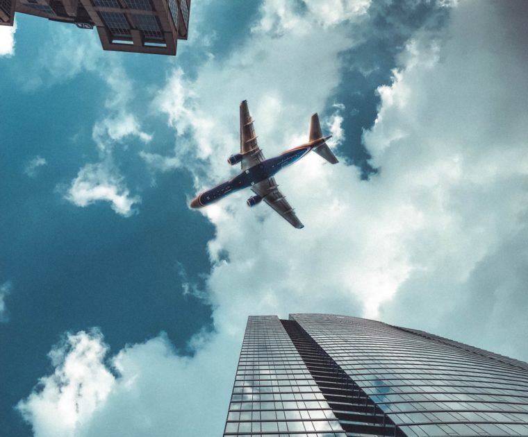 An underbelly view of a plane as it soars in the air over an urban area, with a skyscraper in partial view from the bottom right